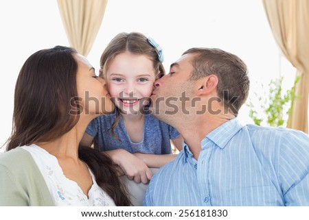 Portrait of happy girl being kissed by parents at home - stock photo