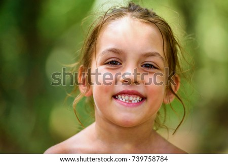 Portrait of happy girl child is smiling enjoying adopted life. Portrait of young girl in nature, park or outdoors. Concept of happy family or successful adoption or parenting.