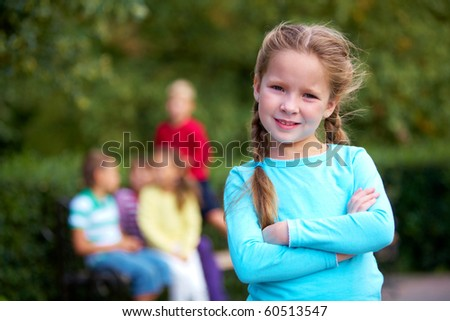 Portrait of happy girl crossing arms and looking at camera with her friends on background - stock photo