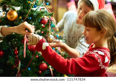 Portrait of happy girl decorating Christmas tree - stock photo