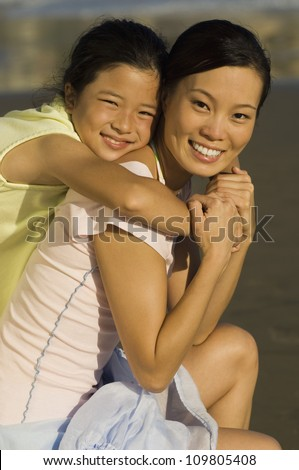 Portrait of happy girl embracing mother on beach - stock photo