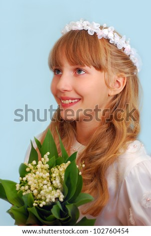 portrait of happy girl going to the first holy communion and posing in studio with bunch of lily of the valley flowers - stock photo