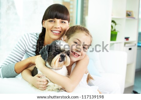 Portrait of happy girl, her mother and their cute pet at home - stock photo