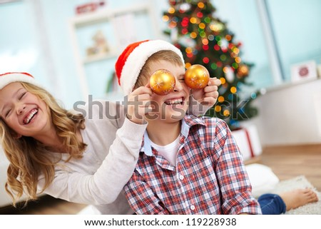 Portrait of happy girl holding decorative toy balls by her brother eyes and both laughing on Christmas evening - stock photo