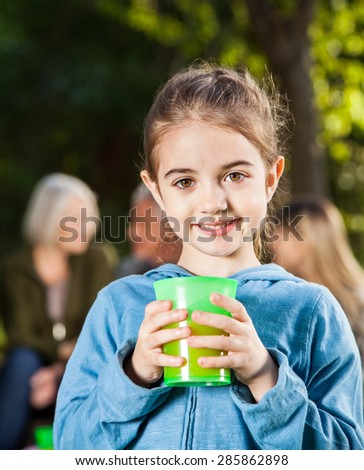 Portrait of happy girl holding glass while family relaxing in background at campsite - stock photo