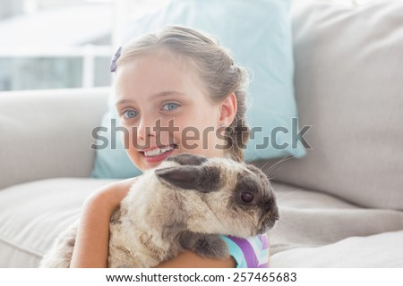 Portrait of happy girl holding rabbit in living room