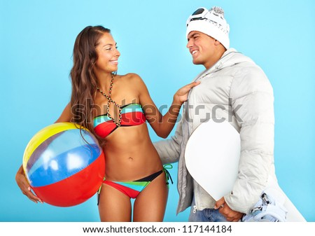 Portrait of happy girl in bikini with ball looking at handsome man in winterwear holding snowboard - stock photo