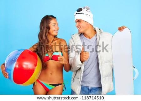Portrait of happy girl in bikini with ball looking at handsome man in winterwear holding snowboard and both showing thumbs up - stock photo