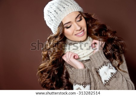 Portrait of happy girl in knitted sweater and hat. Fashion photo - stock photo
