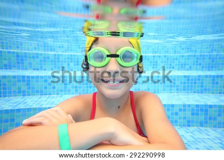 Portrait of happy girl in swimming glasses sitting under water in the pool - stock photo