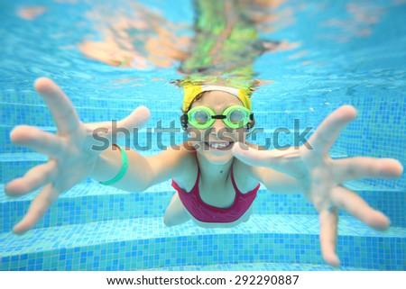 Portrait of happy girl in swimming glasses under water in the pool