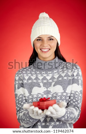 Portrait of happy girl in winterwear holding small red giftbox and looking at camera - stock photo