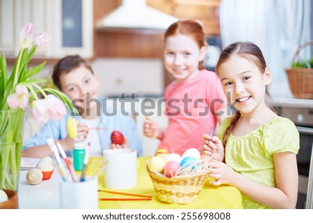Portrait of happy girl looking at camera while painting egg on background of her friends