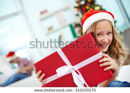 Portrait of happy girl peeking out of big red giftbox on Christmas evening - stock photo