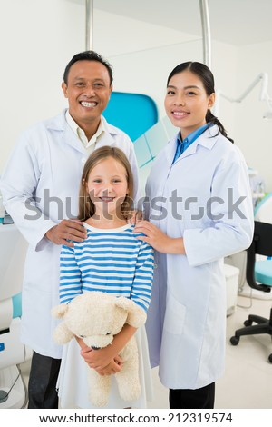 Portrait of happy girl posing with dentist and assistant - stock photo