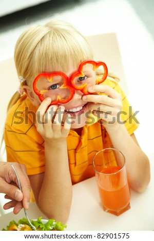 Portrait of happy girl posing with pepper slices by her eyes - stock photo
