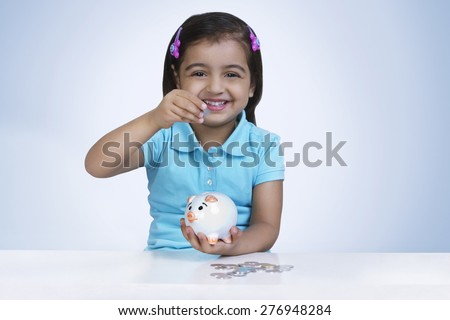 Portrait of happy girl putting coins in piggy bank against blue background - stock photo