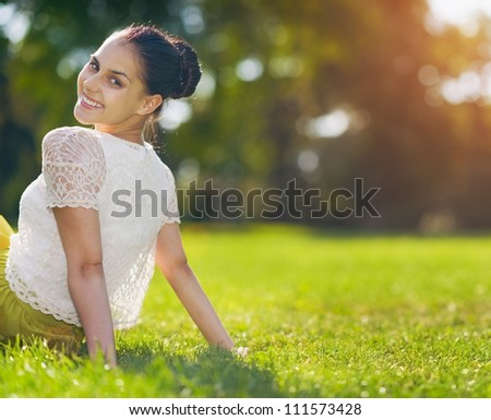 Portrait of happy girl sitting on meadow - stock photo