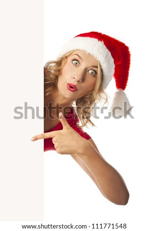 Portrait of happy girl with Christmas hat holding poster and pointing up - stock photo