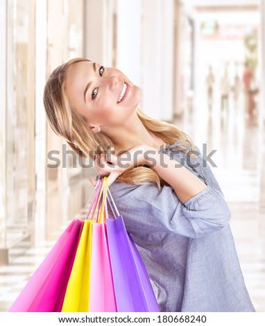 Portrait of happy girl with colorful shopping bag, cheerful young female doing purchase in great luxury retail store, spending money with pleasure concept - stock photo
