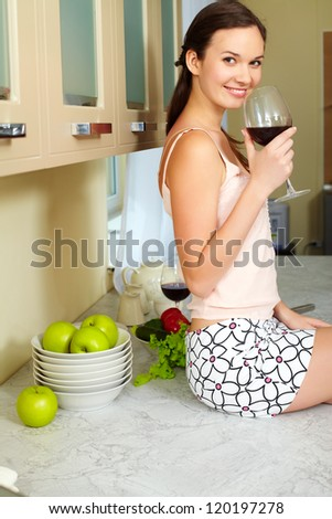Portrait of happy girl with glass of red wine in the kitchen - stock photo