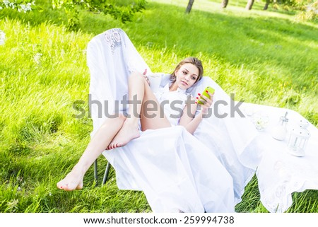 Portrait of Happy girl with long brown hair sitting at white armchair in summer park near table with sweets outdoor in summer cafe drinking coffee and using green cell phone Woman looking at screen - stock photo