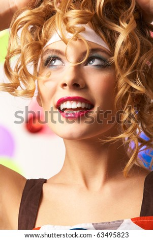 Portrait of happy girl with wavy hair-style touching her head and looking upwards - stock photo
