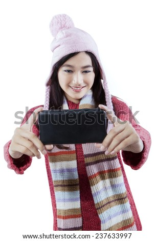 Portrait of happy girl with winter clothes using a mobile phone to take self picture, isolated on white