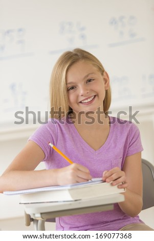 Portrait of happy girl writing notes in book at classroom desk