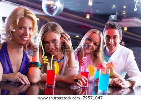 Portrait of happy girlfriends holding glasses with cocktails - stock photo