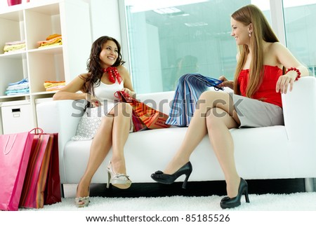 Portrait of happy girlfriends looking at each other while chatting in clothing department