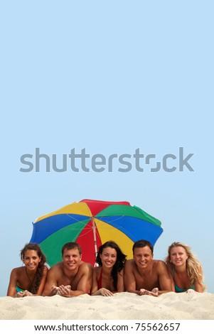 Portrait of happy girls and guys lying on sand under umbrella - stock photo