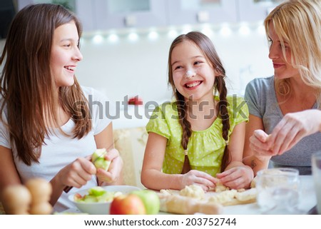 Portrait of happy girls and their mother cooking pastry in the kitchen - stock photo