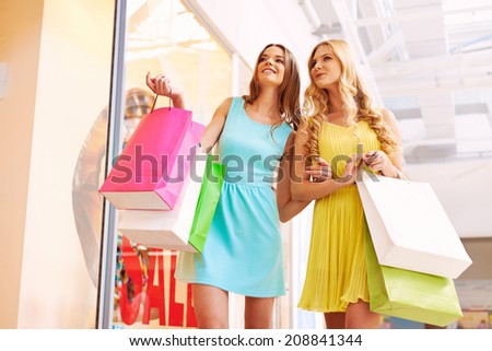 Portrait of happy girls in smart casual with paperbags discussing clothes in shop window - stock photo