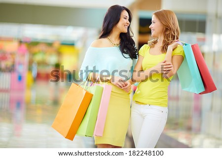 Portrait of happy girls in smart casual with paperbags having a chat in the mall - stock photo