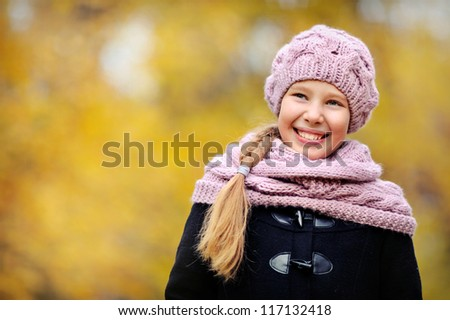 portrait of happy girls. It is in the autumn park. The child has long hair.