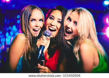 Portrait of happy girls singing in microphone in the karaoke bar  - stock photo