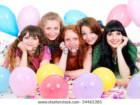 portrait of happy girls with balloons lying on the floor - stock photo