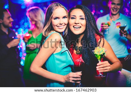 Portrait of happy girls with cocktails looking at camera at party