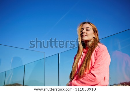 Portrait of happy gorgeous woman posing for the camera while standing against blue sky background with copy space for your text message or content, charming female enjoying sunny afternoon and smiling - stock photo