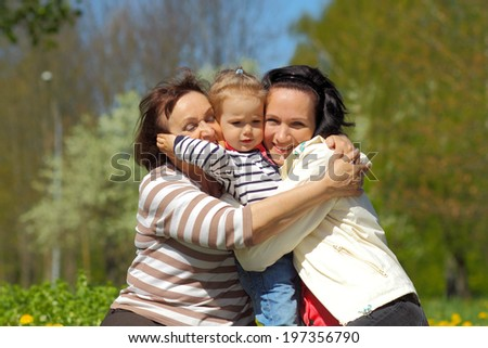 Portrait of happy grandmother, daughter and granddaughter outdoors. Three generations of female. little girl funny hugging her mother and grandmother - stock photo