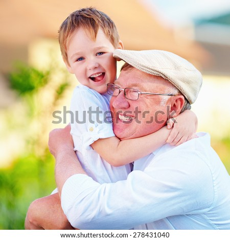 portrait of happy grandpa and grandson embracing outdoors - stock photo