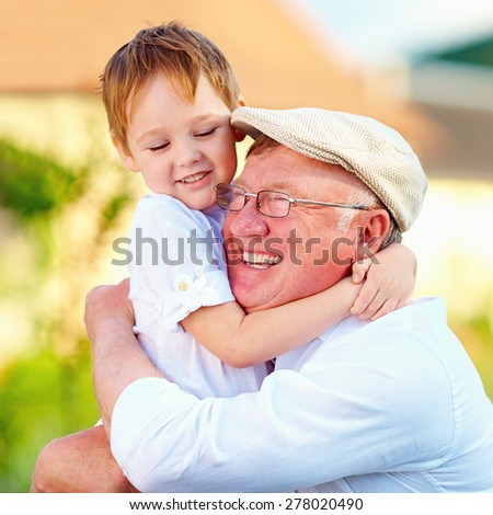 portrait of happy grandpa and grandson embracing outdoors, countryside - stock photo