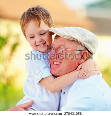 portrait of happy grandpa and grandson having fun outdoors - stock photo