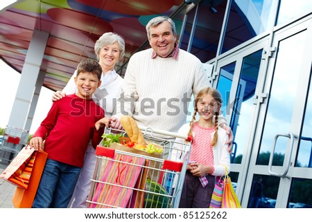 Portrait of happy grandparents and grandchildren with package of food near supermarket - stock photo