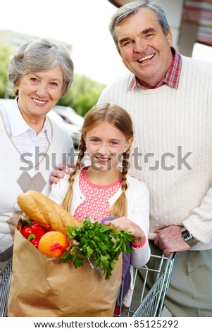 Portrait of happy grandparents and granddaughter after shopping - stock photo