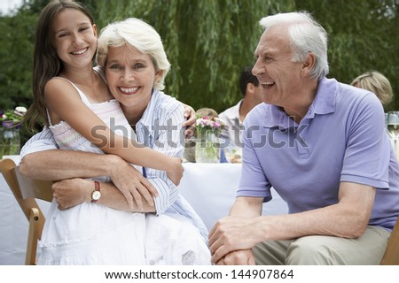Portrait of happy grandparents with granddaughter sitting at table in garden - stock photo
