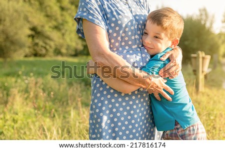Portrait of happy grandson hugging grandmother over a nature outdoor background - stock photo