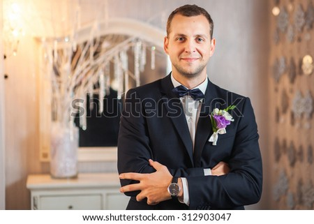 Portrait of happy groom in black suit and looking in camera