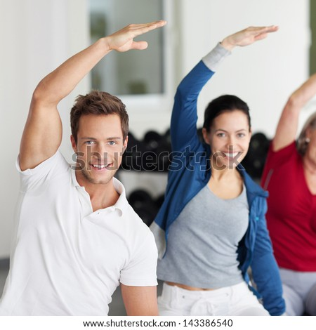 Portrait of happy group with arms raised doing stretching exercise in gym - stock photo